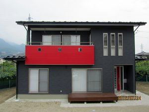 シックな外観に鮮やかな赤を効果的に使ったモダンなお家